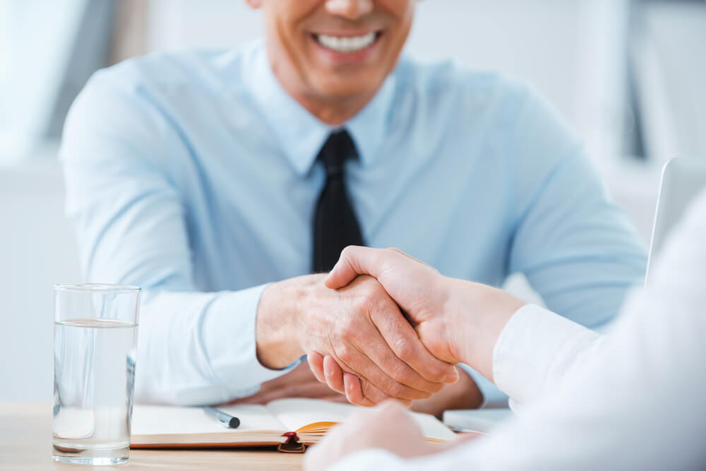 man shaking hands interview asking questions